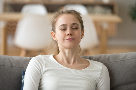 Close up calm peaceful woman relaxing with closed eyes or visualizing, sitting on comfortable sofa, breathing deep, tired girl fall asleep at home, lying on cozy couch, sleeping or taking nap