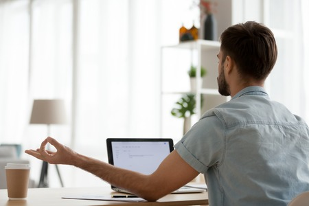 Rear view peaceful man relaxing, meditating at workplace, calm student or freelancer practicing yoga at work or home, good health habit concept, no stress, laptop screen white mock up