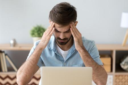 Uomo stanco che soffre di mal di testa dopo un lungo lavoro con il computer portatile, massaggi alle tempie, libero professionista esausto o studente che avverte dolore o pressione sanguigna, malessere, concetto di problema di salute, pausa
