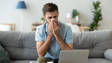 Sick man blowing running nose, holding handkerchief, using laptop at home, sitting in living room on sofa, unhealthy male student, freelancer having allergic reaction or seasonal infection