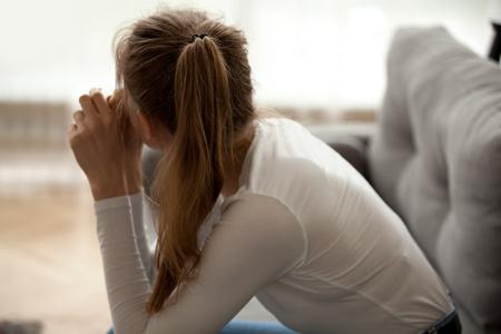 Widok z tyłu zamyślona zamyślona kobieta siedząca samotnie na sofie, zamyślona, zdenerwowana kobieta mająca problem psychologiczny, złamane serce, myśląca o rozwiązaniu problemu, samotna, urażona