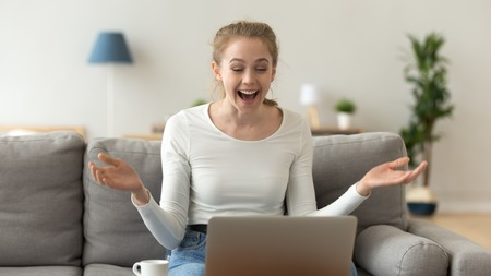 Excited smiling woman looking at laptop screen, receiving good unexpected news, happy female using laptop in living room, sitting on cozy sofa, celebrate online win, victory, business achievement