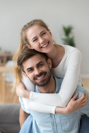 Head shot portrait smiling girlfriend piggyback handsome boyfriend, having fun, spending time together at home, happy wife embrace husband, playing funny game, looking at camera, posing for photo