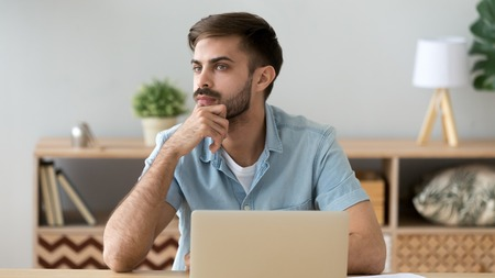 Thoughtful serious student or office worker thinking about online project, sitting at workplace, using laptop, pensive man looking in distance, puzzled freelancer solving business problem Standard-Bild