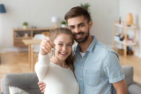 Head shot portrait of happy couple in love holding keys, hugging, standing in living room in new house, looking at camera, satisfied clients posing for photo, wife and husband moving in own apartment