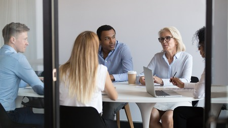 International negotiators or diverse office team staff talking negotiating in boardroom, multiracial business people sitting at conference table discussing deal at group meeting behind glass door Stock Photo