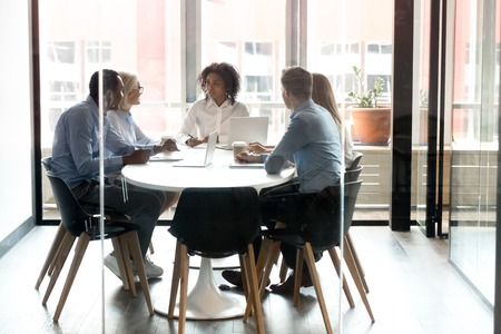Multiracial business team people with african female leader talk sit at modern office boardroom table, diverse employees discuss work plan together at corporate staff group meeting behind glass door Standard-Bild - 120839046