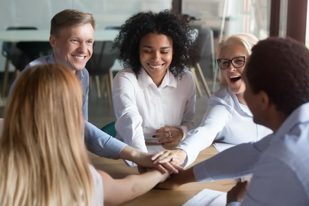 Happy multi ethnic employees stacking hands in pile with coach mentor engaged in team building, multicultural office workers people group promise unity help loyalty teamwork at motivational training