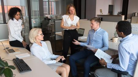 Capo squadra capo maschio serio che discute il nuovo piano di marketing con i dipendenti in ufficio, mentore allenatore leader d'affari concentrato che parla con diversi lavoratori che spiegano le scartoffie al gruppo stand up meeting