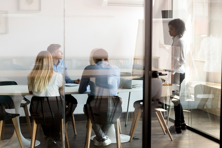 Female african american leader mentor give flip chart presentation at diverse team training behind glass door, mixed race lady business coach teacher speak consult employees group at office meeting