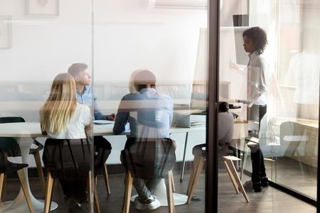 Une femme leader afro-américaine mentor donne une présentation sur un tableau à feuilles mobiles lors d'une formation d'équipe diversifiée derrière une porte vitrée, une enseignante d'entraîneur d'affaires de race mixte parle consulter le groupe d'employés lors d'une réunion de bureau