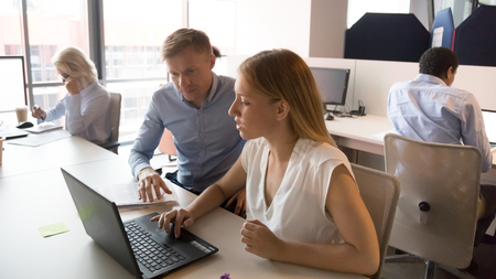 Female manager consult client in modern corporate office with laptop at business meeting, focused coworkers team colleagues mentor help intern instruct trainee talk discuss computer work at workplace