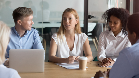 Confident female business leader consulting negotiating with clients talking to colleagues at diverse corporate group meeting reporting about work result presenting business offer at conference table.
