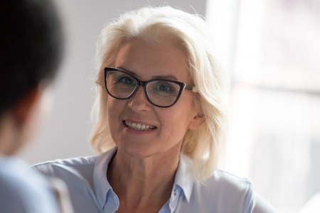 Smiling middle aged businesswoman in glasses looking at colleague client at business meeting, happy focused old senior female leader coach mentor teacher listening to partner having conversation