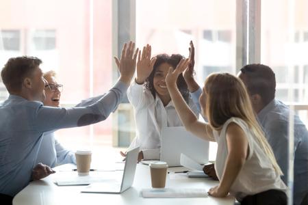 La gente feliz del equipo ejecutivo multicultural choca los cinco, el grupo de empleados de oficina diversos y motivados comprometidos con el espíritu de trabajo en equipo, la promesa de confianza, la integridad, celebran el éxito empresarial compartido, el concepto de victoria Foto de archivo