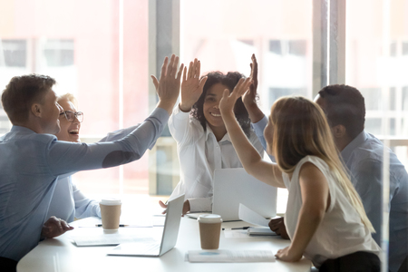 Le persone felici del team esecutivo multiculturale danno il cinque, diversi dipendenti d'ufficio motivati gruppo impegnato nello spirito di teambuilding promettono fiducia integrità celebrano il successo aziendale condiviso vincere il concetto Archivio Fotografico