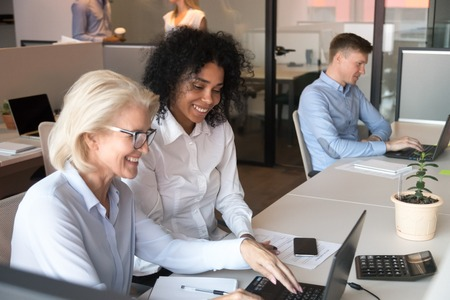 Smiling old mature businesswoman professional mentor teacher manager consulting african american client instructing helping intern teaching new employee working on laptop at business office workplace.