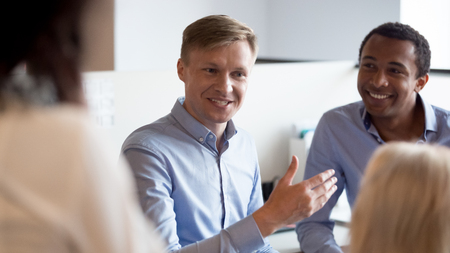 Smiling businessman mentor coach speaking to diverse colleagues employees at office meeting share ideas, confident team leader talking to workers group having fun business conversation with coworkers