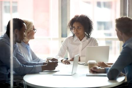 Une dirigeante afro-américaine sérieuse parlant lors d'une réunion de conseil d'administration de divers groupes, des employés d'équipes multiethniques discutant des avantages de l'accord, négociant les termes du contrat commercial avec les clients