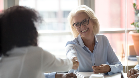 Happy mature caucasian company team leader boss handshake african american employee business partner make work deal agreement with client shaking hands over negotiations table at group office meeting.