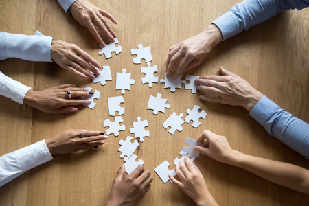 Diverse business team people hands assemble puzzle together connect pieces at desk, employees collaborate find common solution engaged help contribute in effective teamwork concept top close up view