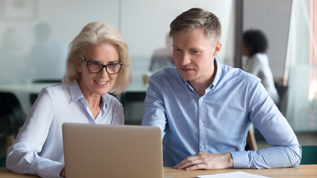 Middle aged bank manager saleswoman make business offer to client showing deal benefit on laptop, old executive mentor consulting new employee talk collaborate with colleague on computer in office Stock Photo
