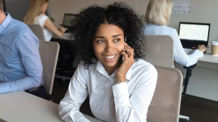 Smiling african american young employee businesswoman talking on phone having mobile conversation sitting in modern office with coworkers, happy mixed race female worker chatting by cellphone at work