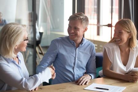 Alte Maklerin, Bankmanagerin, glückliche junge Paarkunden machen Geschäftsversicherungs-Investitionsgeschäft, Familienkunden unterzeichnen Hypothekendarlehensvertrag, schütteln die Hand mit dem Beratungsberater Standard-Bild