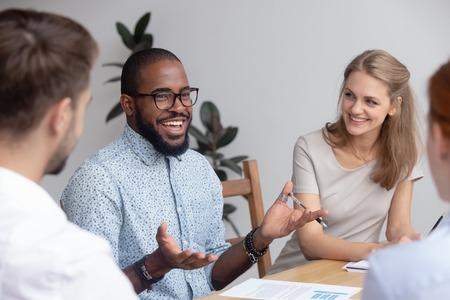 Fröhlicher selbstbewusster afrikanischer männlicher Business-Coach, der ein vielfältiges Team-Meeting-Seminar leitet, das über gute Arbeitsergebnisse spricht, motiviert Mitarbeiter, schwarzer Mentor, der mit der Büroangestelltengruppe beim Workshop-Training spricht talking