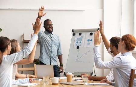 El concepto de votación del equipo de negocios, el líder del entrenador africano sonriente y el grupo de empleados diversos levantan la mano comprometidos en el voluntariado que toma una decisión unánime participar en la capacitación de presentación corporativa