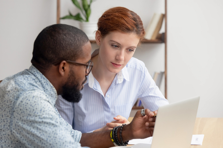 African american mentor salesman broker consultant explaining computer work to caucasian intern working with client showing online presentation looking at laptop negotiate on project or business deal. Stock Photo