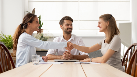 Happy female business partners shake hands sign two contracts with lawyer mediation at meeting, smiling businesswomen handshake make legal partnership deal after successful negotiations with mediator
