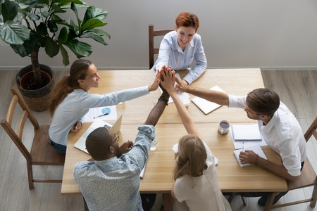 Happy united diverse business team people group give high five together sit at office table celebrate goal achievement, company partnership, triumph in teamwork, corporate victory concept, top view Stock Photo