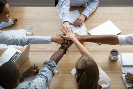 Team people stacking hands in pile together over table engaged in partnership teambuilding, diverse office employees group promise support unity trust loyalty in teamwork concept, close up top view Stock Photo