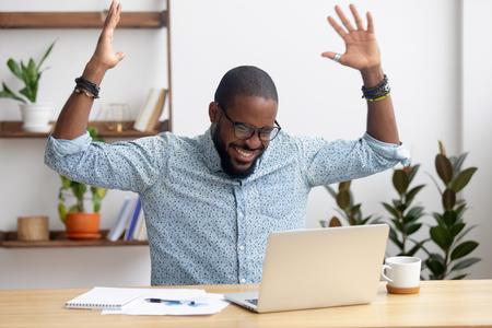 Euforyczny zachwycony afrykański czarny biznesmen szczęśliwy, że czyta wspaniałe wiadomości online awansuje nagradzany świętuje sukces biznesowy wygrana licytacja, podekscytowany dobrymi wynikami pracy, czujący zmotywowany zwycięzca