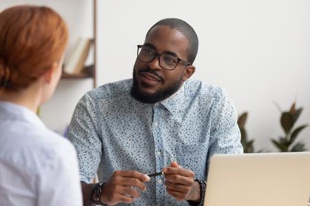Responsabile delle risorse umane africano che ascolta la candidata caucasica che fa domande al colloquio di lavoro, incontro di lavoro, datore di lavoro di reclutamento diversificato e cliente cercatore che parla, risorse umane, concetto di reclutamento
