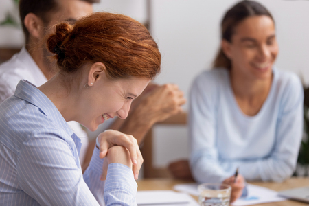 Happy cheerful business woman laughing at funny joke at group negotiations enjoy friendly team building talk at company meeting, smiling employee having fun positive emotions with office colleagues Standard-Bild