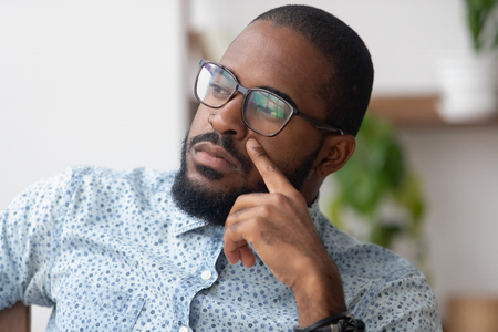 Thinking of solution concept, pensive serious african american businessman looking away deep lost in thoughts, thoughtful dreamy or doubtful black man searching new ideas planning business vision