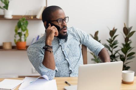 Ernster afroamerikanischer Geschäftsmann, der am Telefon sitzt und mit Laptop am Schreibtisch sitzt, fokussierter schwarzer Manager, der Geschäftsanrufe tätigt und mobile Gespräche über das Mobiltelefon führt, die den Kunden kontaktieren