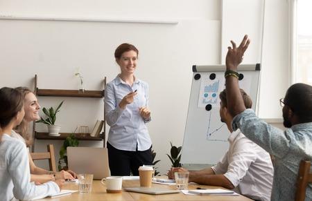 Participante del taller afroamericano levantar la mano y preguntar al entrenador en la capacitación de la conferencia corporativa, el voluntario del empleado negro se compromete a participar en la discusión, el concepto de educación empresarial