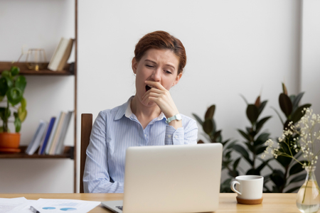 Sleepy bored business woman yawning at workplace feeling deprived in office, tired lazy drowsy female worker gaping suffer from fatigue, no energy motivation, chronic lack of sleep overwork concept Stock Photo