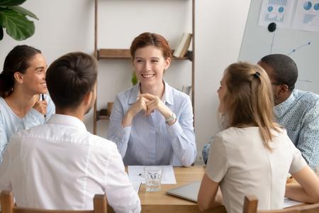 Fröhliche Unternehmensleiterin und vielfältige Geschäftsteamleute, die bei Gruppenbürositzungen freundliche Gespräche führen, Mitarbeiterpraktikanten, Studenten, die sich unterhalten, teilen kreative Ideen mit Mentorlehrer