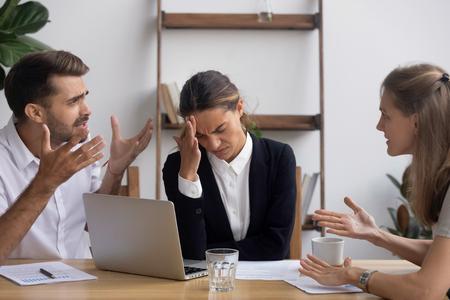 Un employé de bureau stressé et agacé ayant une migraine lors d'une réunion d'affaires avec un client se plaignant fatigué des collègues en colère qui se disputent en criant un conflit sur le lieu de travail.