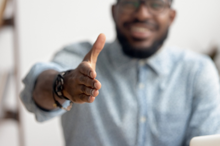 African american black professional business man hr recruiter consultant extending hand at camera for handshake concept greeting offering cooperation, welcoming at job interview, close up view Stock Photo