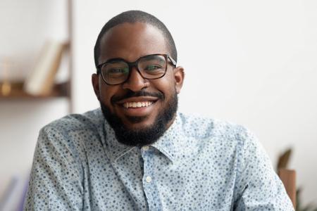 Feliz hombre de negocios negro afroamericano hr e entrenador sonriendo hablando mirando a la cámara web haciendo videollamadas de conferencia, entrevista de trabajo en línea, seminario web de blogs de tiro, retrato de disparo a la cabeza