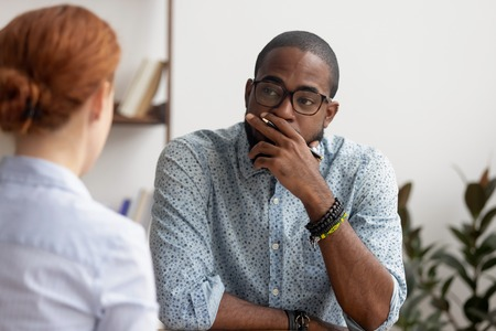 Doubtful unconvinced african american hr manager talking to caucasian applicant at job interview feeling skeptic rejecting seeker skill, bad first impression, lack of experience or failed performance