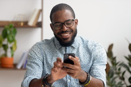 Happy african american businessman using phone mobile corporate apps at workplace texting sms, smiling black man looking at smartphone browsing internet, office technology and digital communication Stock Photo