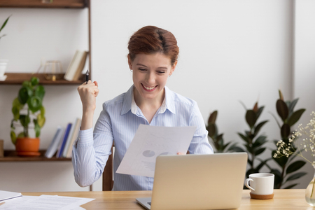 Happy businesswoman celebrate business success motivated by great achievement work result looking at financial report, excited entrepreneur satisfied with profit growth in document with project stats Stock Photo