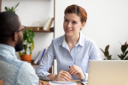 Smiling woman hr recruiting company manager listening to african job seeker applicant at job interview, satisfied recruiter talk with candidate making hiring decision, staffing, good first impression