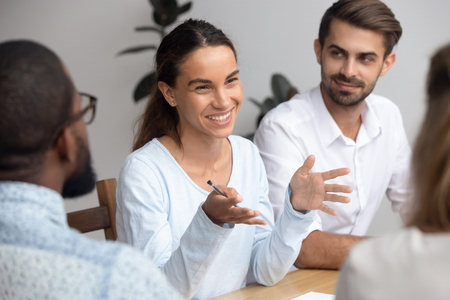 Happy friendly woman team leader coach mentor talking to employees group at office meeting smiling offering idea teaching interns or reporting at briefing seminar having fun business conversation. Standard-Bild